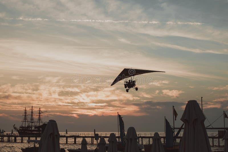 Parapendio nel cielo Tandem dell'aliante che sorvola il mare con acqua blu e le montagne nel giorno soleggiato luminoso fotografia stock