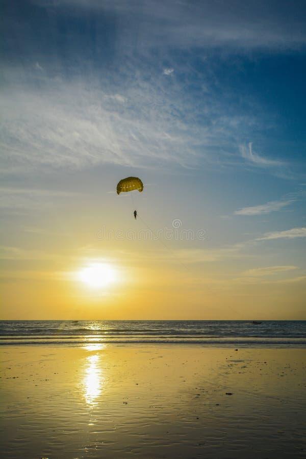 Parapendio sopra il mare nel tempo di tramonto fotografia stock libera da diritti