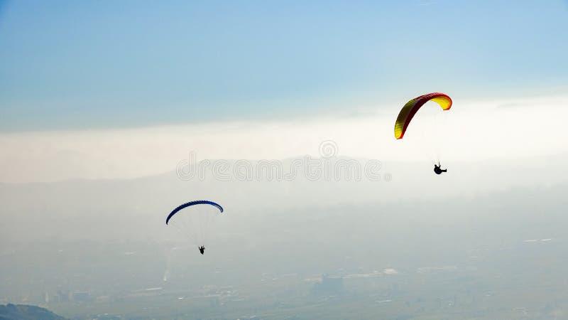 Parapente de dois paragliders acima do vale enevoado foto de stock royalty free