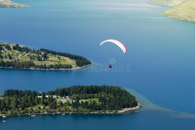 Parapente em tandem sobre o lago Wakatipu em Queenstown, Nova Zelândia imagem de stock