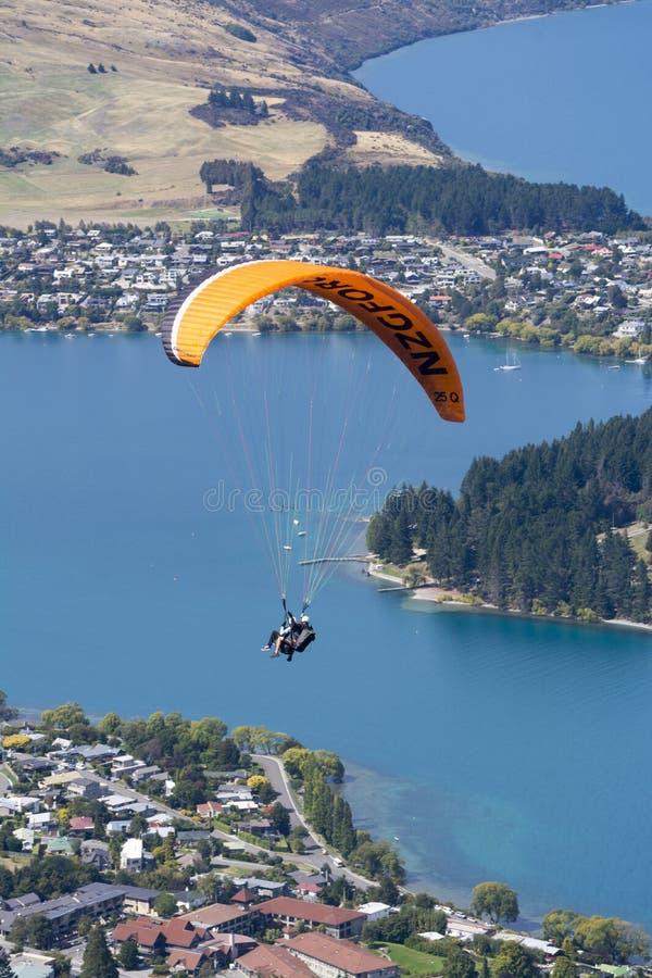 Parapente em tandem sobre o lago Wakatipu em Queenstown, Nova Zelândia fotografia de stock royalty free