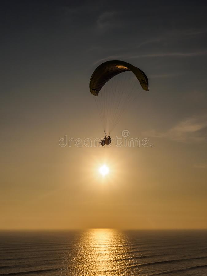Parapente nos penhascos da cidade de Lima durante o por do sol imagem de stock royalty free