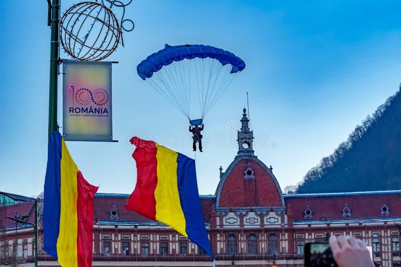 Parapentiste apportant le drapeau roumain devant le bâtiment de préfecture de Brasov photo stock