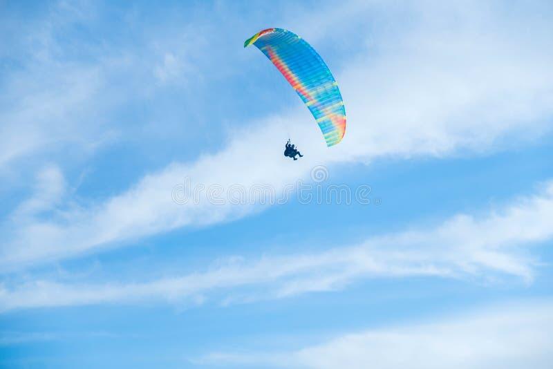 Parapentistes dans le ciel bleu lumineux, le tandem de l'instructeur et le débutant photographie stock