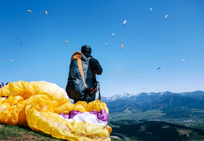 Paraplanner in full equipment for flight looks on soaring another paraplanes in sky royalty free stock photos