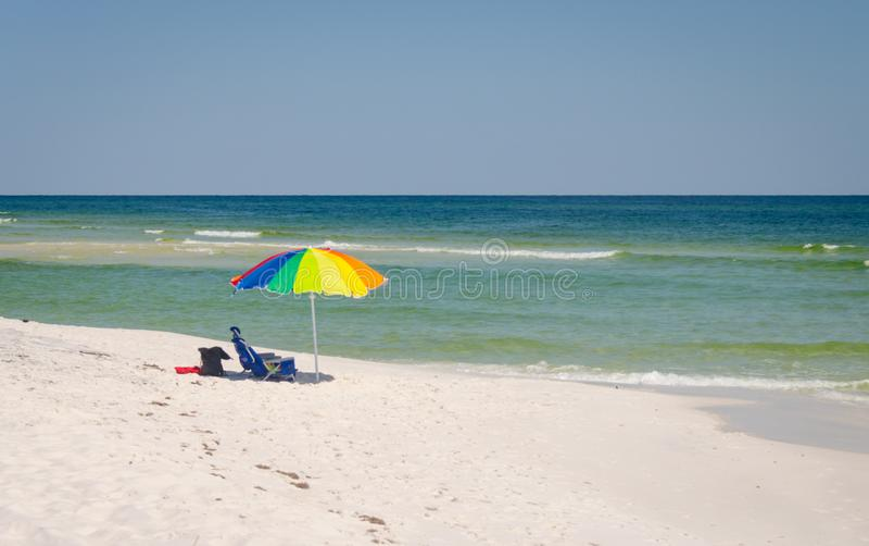 Paraplu en stoelenopstelling bij strandoever stock fotografie