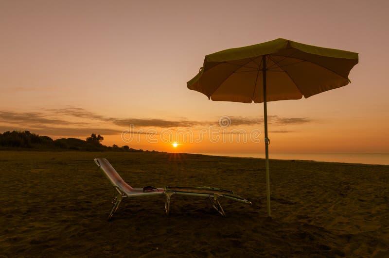Paraplu op het strand bij zonsondergang stock afbeelding