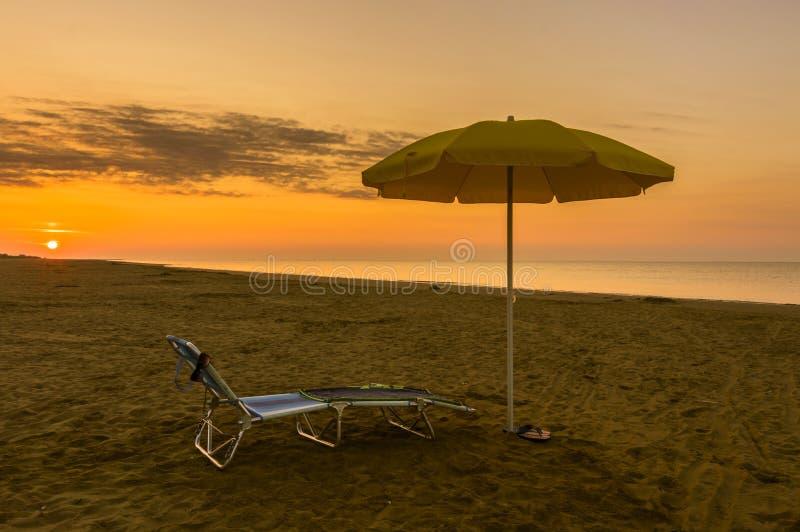 Paraplu op het strand bij zonsopgang royalty-vrije stock afbeeldingen
