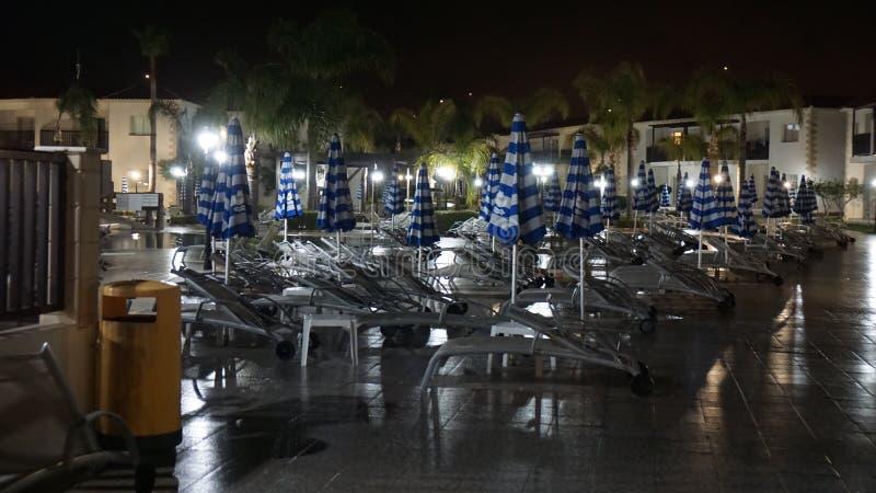 Paraplu's en sunbeds door de poolparaplu's in de avond stock foto's