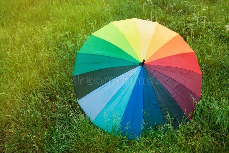 Parapluie coloré d'arc-en-ciel au-dessus d'une pluie d'été de ressort de l'espace de copie de Sunrisez de champ d'herbe verte photos stock