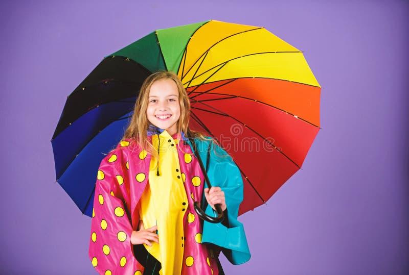 Parapluie coloré de prise heureuse de fille d'enfant utiliser le manteau imperméable Appréciez le temps pluvieux avec les vêtemen image stock