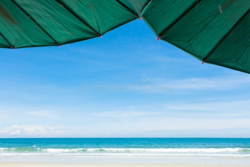 Parapluie contre la plage avec le ciel bleu image libre de droits