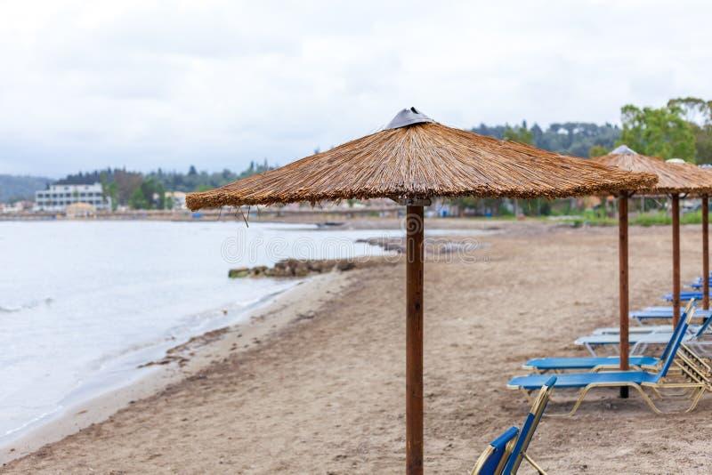 Parapluie de Bonita empilant dans la plage Chaises paresseuses portatives diplay sous la hutte et faire face au rivage agréments  photos stock