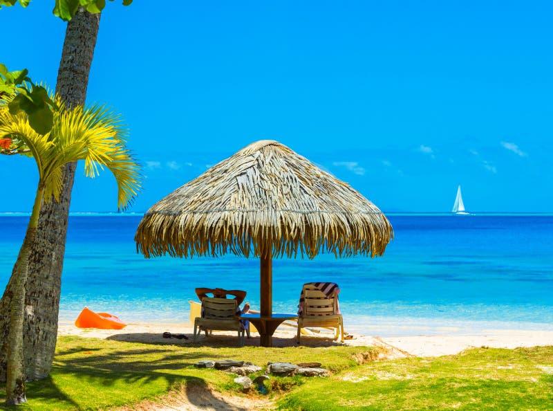Parapluie de paille sur la plage dans la lagune Huahine, Polynésie française photo libre de droits