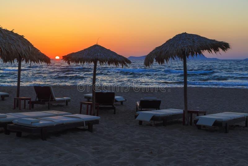 Parapluie de plage au coucher du soleil, à la vue des chaises et aux parapluies sur la plage Coucher du soleil en mer beau ciel s image stock