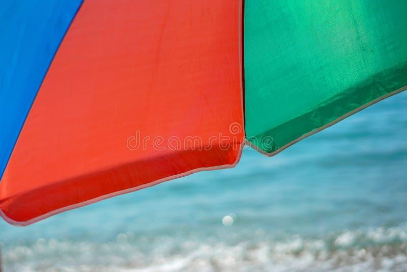 Parapluie de plage coloré contre le ciel bleu ensoleillé photographie stock