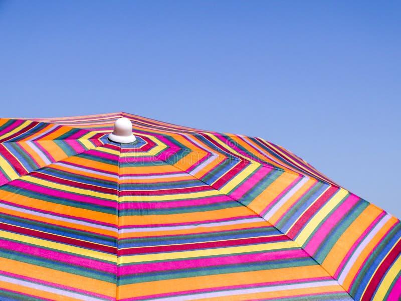 Parapluie de plage coloré contre le ciel bleu Texture rayée photo libre de droits