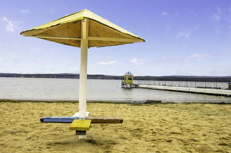 Parapluie de plage et pilier jaune images libres de droits