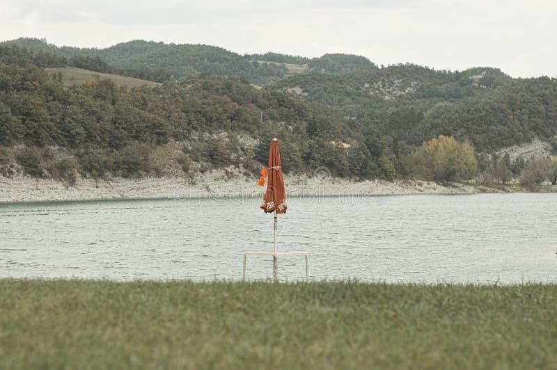 parapluie de plage rouge sur le rivage du lac Fiastra images stock