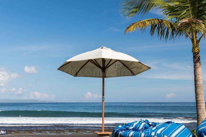 parapluie de plage un jour ensoleill mer l 39 arri re plan plage tropicale avec le sable noir. Black Bedroom Furniture Sets. Home Design Ideas