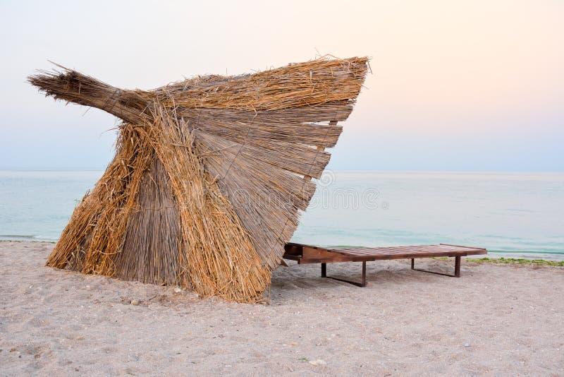 Parapluie de Reed sur la plage dans le coucher du soleil photographie stock