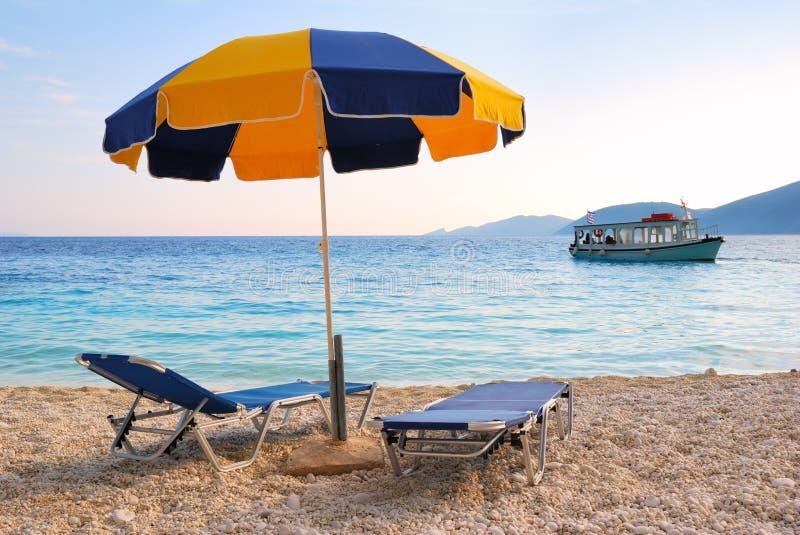 Parapluie de soleil coloré et deux lits pliants sur une plage photographie stock