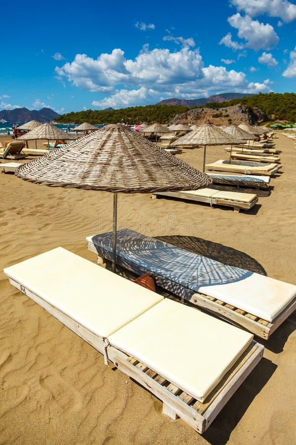 Parapluie de soleil de paille avec le canapé du soleil sur la plage sablonneuse du je photographie stock libre de droits