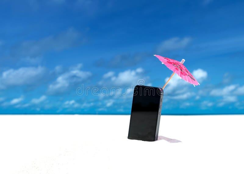 Parapluie de téléphone portable et de cocktail sur la plage avec la mer photo stock