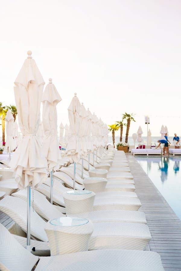 Parapluie et cabriolet-lonque blancs près de piscine au temps de coucher du soleil photo stock