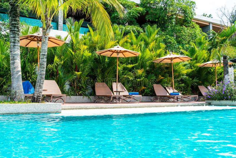 Parapluie et chaise autour de piscine dans l'hôtel et la station de vacances photos stock
