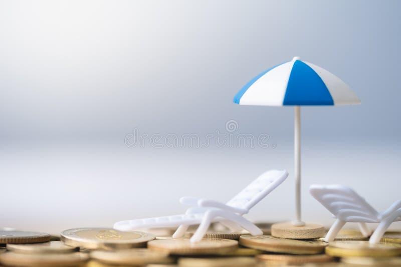 Parapluie et chaise sur la pile de pièces de monnaie photos stock