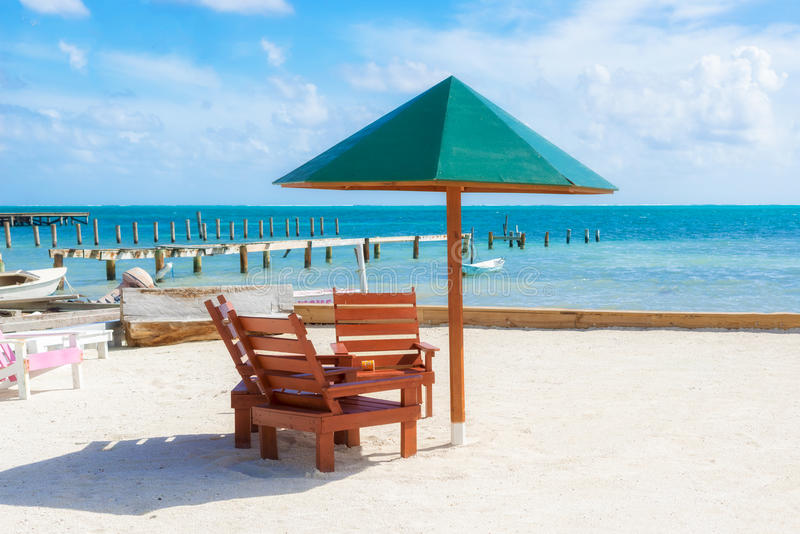 Parapluie et chaises sur la plage dans le matoir de Caye, Belize images stock