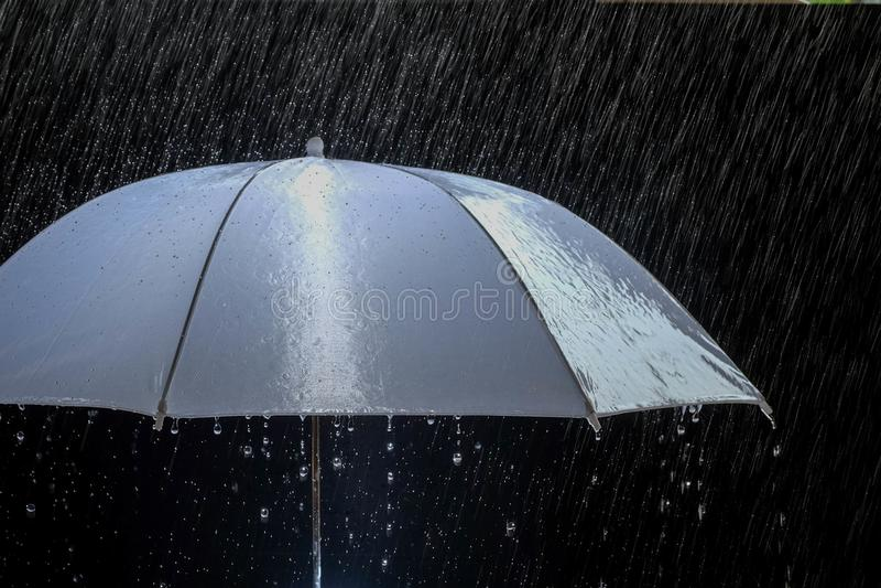 Parapluie humide de protection par temps orageux avec l'orage naturel, sur le fond noir, photographie stock libre de droits