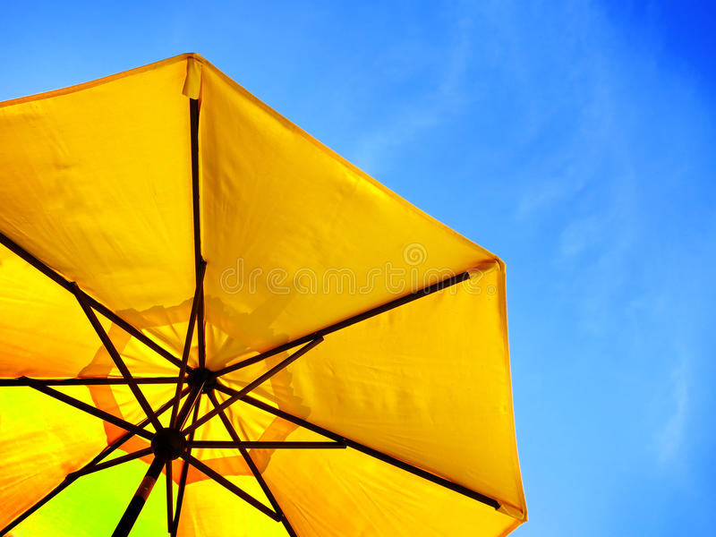 Parapluie jaune et ciel bleu photographie stock