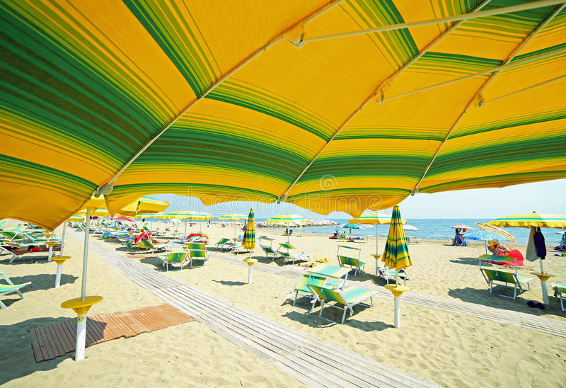 parapluie jaune sur la plage ensoleillée en été photos stock