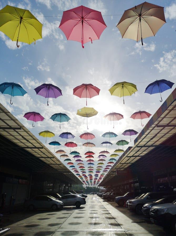 Parapluie multicolore accrochant au-dessus du toit dans toute la rue un beau jour bleu photo stock