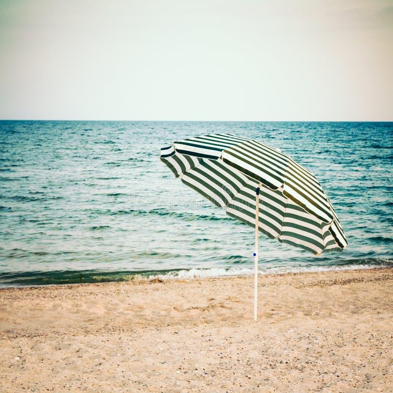 Parapluie rayé sur la plage sablonneuse image libre de droits