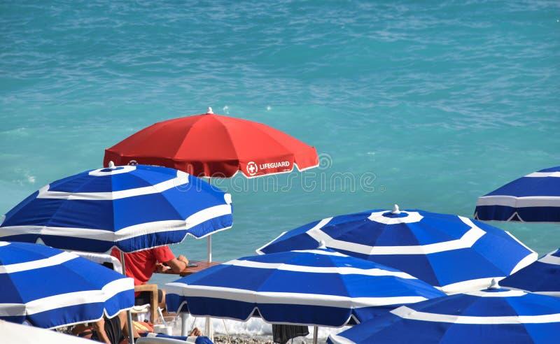 Parapluie rouge de parasol de maître nageur sur le bleu photo stock