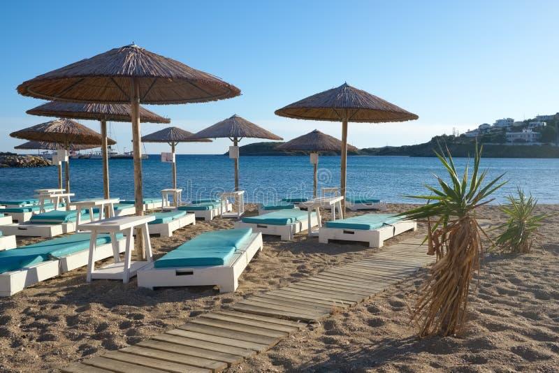 Parapluies avec des lits pliants sur la belle plage sablonneuse avec l'eau de mer de turquoise dans le village pittoresque de Bat photos stock