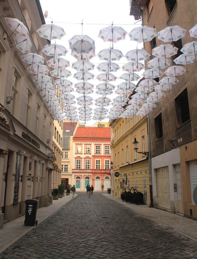 Parapluies blancs accrochant au-dessus d'une rue au centre historique de Bratislava image stock