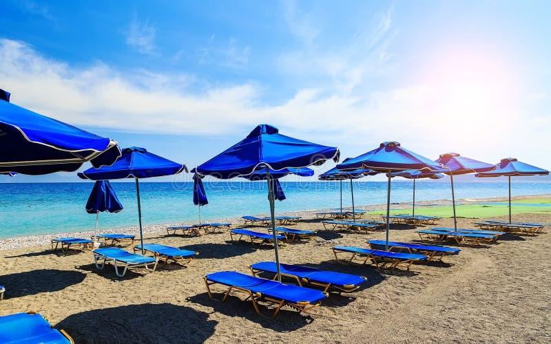 Parapluies de plage colorés avec des chaises de plate-forme Pebble Beach et île dans la distance photos libres de droits
