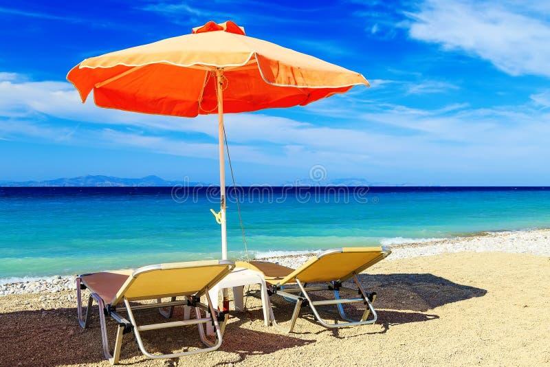 Parapluies de plage colorés avec des chaises de plate-forme Pebble Beach et île dans la distance photographie stock libre de droits