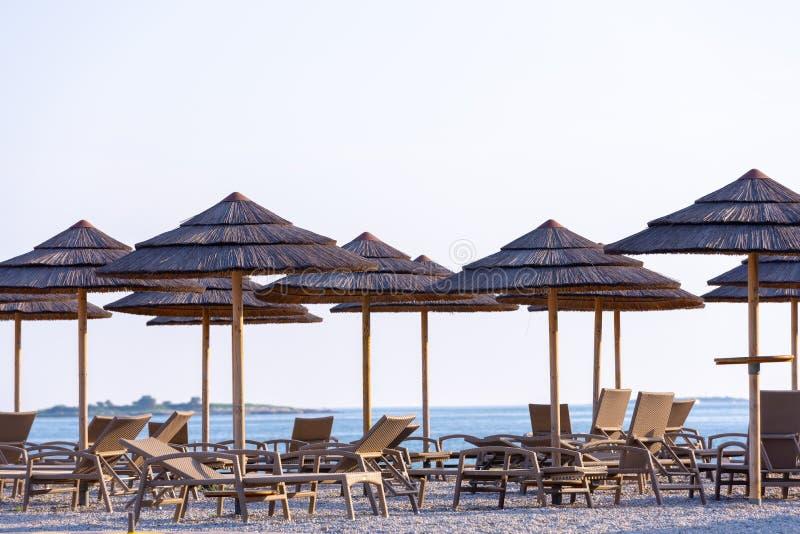 Parapluies de Reed et chaises de plate-forme sur la plage photos stock