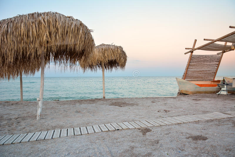 Parapluies de Reed sur la plage dans le coucher du soleil photographie stock