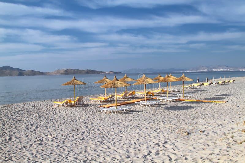 Parapluies de roseau sur la plage de soirée de l'île de Kos photo libre de droits
