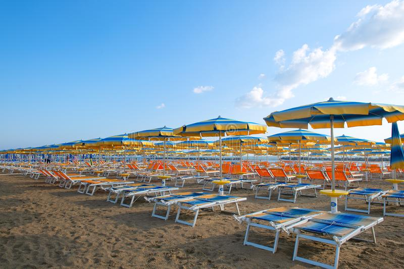 Parapluies et canapés du soleil sur la plage en Adriatique Romagna la Riviera en Italie images stock