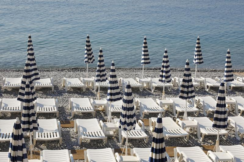 Parapluies et chaises de plage rayés image stock
