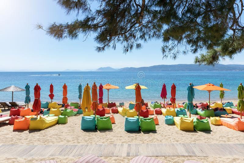 Parapluies et chaises longues colorés à la plage d'Agia Eleni, île de Skiathos images stock