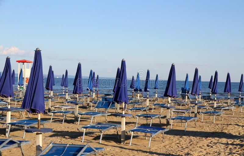 Parapluies et chaises longues sur la plage au coucher du soleil sur le bord de la mer photos stock