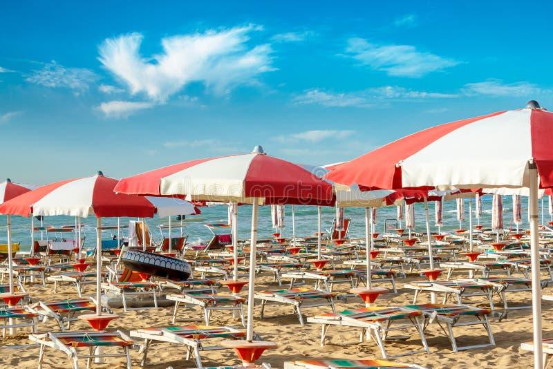 parapluies et sunlongers sur la plage sablonneuse photos stock